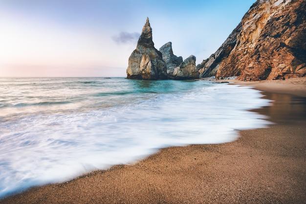 Portugal ursa beach. stosy morskie, biała fala oceanu oświetlona światłem zachodzącego słońca.