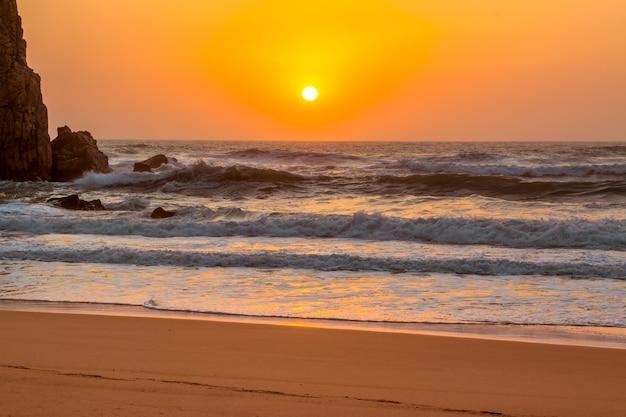 Portugalia. piaszczysta plaża w pobliżu cape roca. skała i fale. słońce zachodzi w oceanie