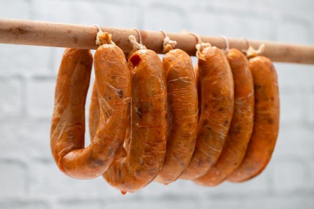 Portugalskie wędzone kiełbaski alheira na drewnianym patyku