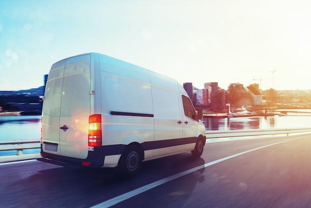 Poruszająca się furgonetka na autostradzie z tłem miasta. renderowanie 3d