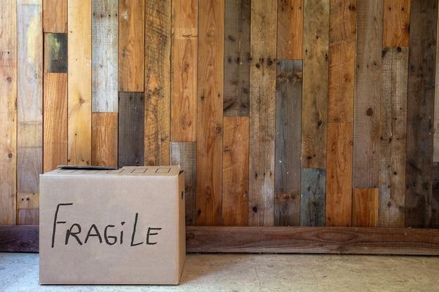 Poruszające się pudełko z napisem fragile przy drewnianej ścianie