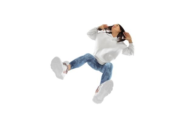 Poruszający. młoda stylowa kobieta w nowoczesnym stroju w stylu ulicznym na białym tle, strzał od dołu. kaukaski modny model w butach i kombinezonach, muzyk, raper występujący.