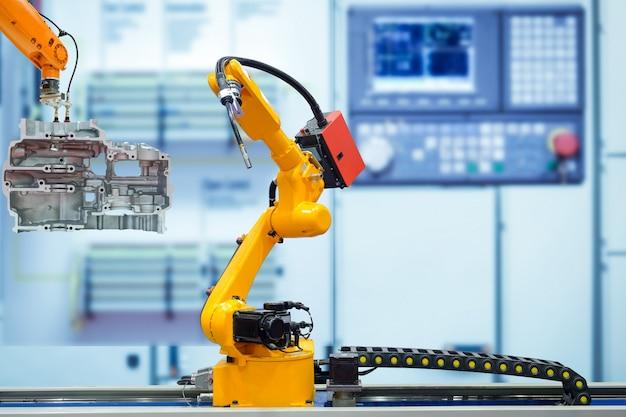 Poruszający robot spawalniczy i chwyt robota pracujący z częściami silnika motocykla na niewyraźnym inteligentnym, fabrycznym błękicie