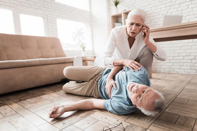 Poruszona dojrzała kobieta wzywa pogotowie dla starszego mężczyzny.