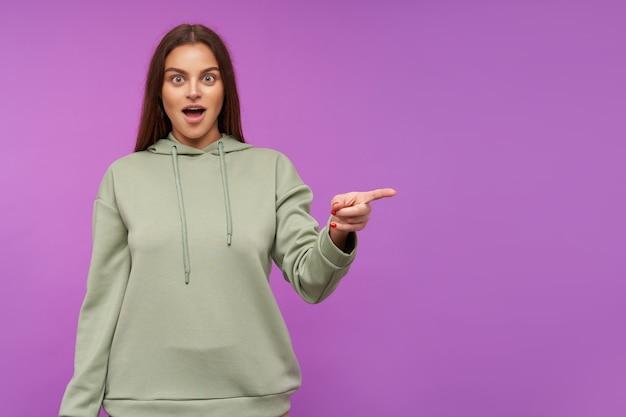 Poruszona młoda atrakcyjna brunetka kobieta z luźnymi włosami, patrząc zdziwiona z przodu, odgarniając na bok, stojąc nad fioletową ścianą w zwykłych ubraniach