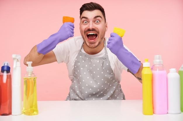 Poruszony, młody, dość krótkowłosy brunetka mężczyzna wyglądający podekscytowany z szeroko otwartymi oczami i ustami oraz podnoszący ręce gąbkami czyszczącymi, odizolowany na różowo