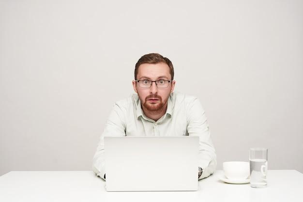 Poruszony, młody, krótkowłosy, brodaty mężczyzna w okularach, trzymając ręce na klawiaturze laptopa, patrząc zaskoczony na aparat, na białym tle nad białym
