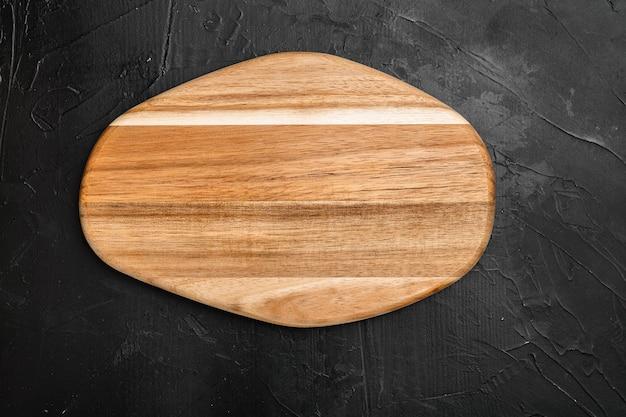 Porysowany zestaw desek do krojenia, na czarnym tle ciemnego kamiennego stołu, płaski widok z góry, z miejscem na kopię tekstu lub produktu