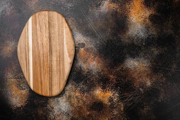 Porysowany zestaw desek do krojenia, płaski widok z góry, z kopią miejsca na tekst lub jedzenie, na starym ciemnym, rustykalnym tle stołu