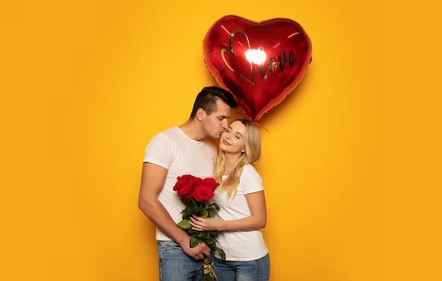 Ð¡porzucone zdjęcie uroczej damy i jej przystojnego chłopaka, który całuje ją w policzek, a jednocześnie daje jej bukiet róż i duży czerwony balon w kształcie serca.