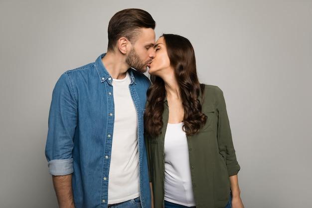 Ð¡porzucone zdjęcie uroczej kobiety o kasztanowych włosach, która całuje swojego przystojnego chłopaka w policzek, jednocześnie przytulając go od tyłu.