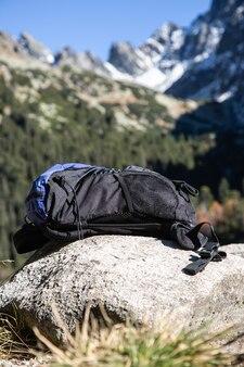 Porzucony plecak turystyczny postawiony na skale w górach.