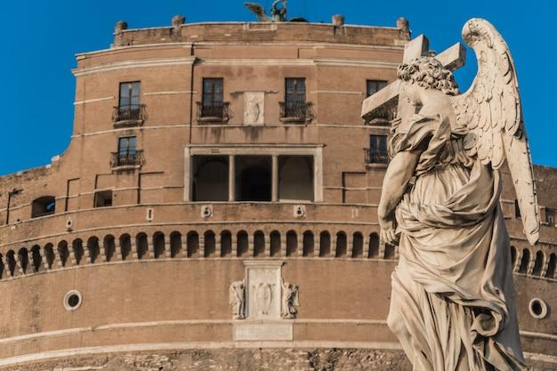 Posąg anioła z krzyżem, zamek świętego anioła na tle