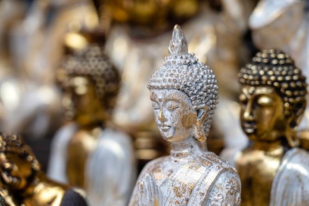 Posąg buddy figurki pamiątkowe na wystawie na sprzedaż na targu ulicznym w ubud, bali, indonezja. wystawa rękodzieła i sklepu z pamiątkami, z bliska