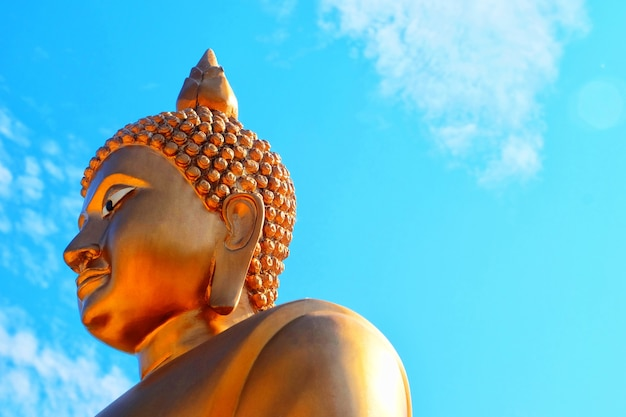 Posąg buddy obraz buddy używany jako amulety religii buddyzmu w tajlandii. stojący złoty budda i błękitne niebo.