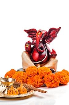 Posąg hinduskiego boga ganesha z układem kultu na białej powierzchni.