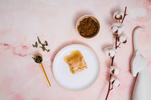 Posąg jednorożca; ziarna kawy; odchodzi; gałązka bawełny z plastra miodu na ceramice przed różowym tle z teksturą