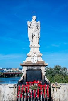Posąg świętego ze świecami i kwiatami u jego stóp, a za nim błękitne niebo i rzeka