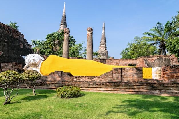 Posągi buddy są białe, pokryte żółtą szatą, śpią pośród starożytnych ruin w świątyni wat yai chai mongkon w parku historycznym phra nakhon si ayutthaya, prowincja ayutthaya, tajlandia