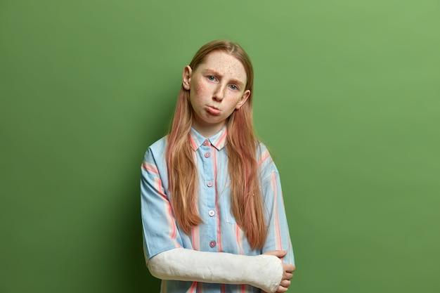 Posępna, niezadowolona dziewczynka ma zły nastrój, ubrana niedbale, przechyla głowę i zaciska usta, nosi gips, jest kontuzjowana po ryzykownym sporcie, wyraża negatywne emocje, izolowana na zielonej ścianie