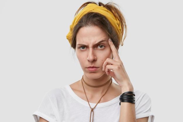Posępna niezadowolona kaukaska kobieta unosi brwi, trzyma rękę w pobliżu skroni, próbuje zrozumieć jakieś informacje