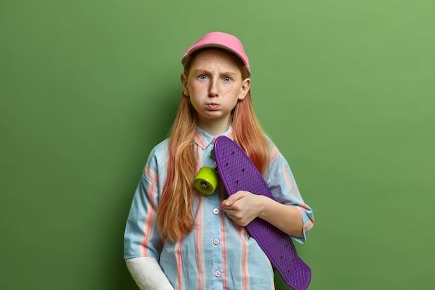 Posępna, niezadowolona preteen dziewczyna na deskorolce pozuje na deskorolce, ma zły humor po złamaniu ręki podczas jazdy na deskorolce, nie może cieszyć się ulubionym hobby z powodu poważnych kontuzji. pechowy odpoczynek