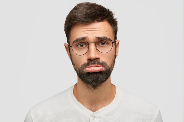 Posępny, nieogolony mężczyzna z niezadowolonym wyrazem twarzy, wykrzywia dolną wargę, ma żałosny wyraz twarzy