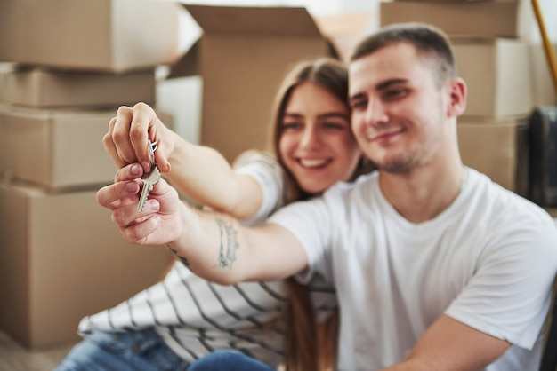 Posiada klucze do ich nowego domu. ludzie sukcesu. wesoła młoda para w swoim nowym mieszkaniu. koncepcja ruchu.