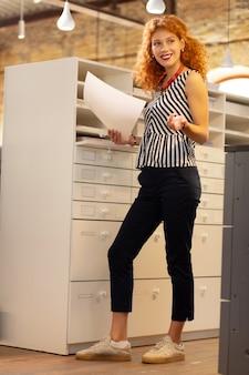 Posiadanie dokumentów. stylowa bizneswoman nosząca ładny naszyjnik uśmiechnięta trzymająca dokumenty