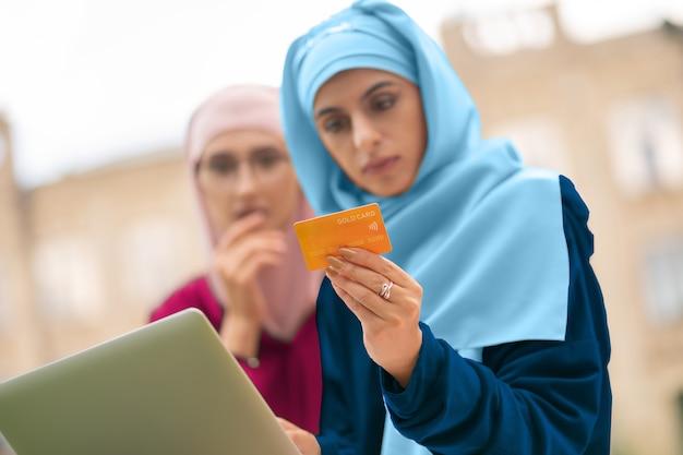 Posiadanie karty bankowej. dwie młode muzułmanki trzymające kartę bankową podczas zakupów online na zewnątrz