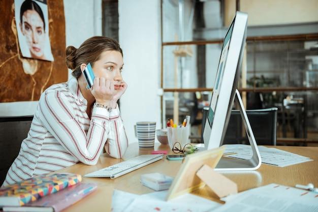 Posiadanie karty debetowej czarnowłosa odnosząca sukcesy bizneswoman trzymająca swoją kartę debetową przed zakupami online