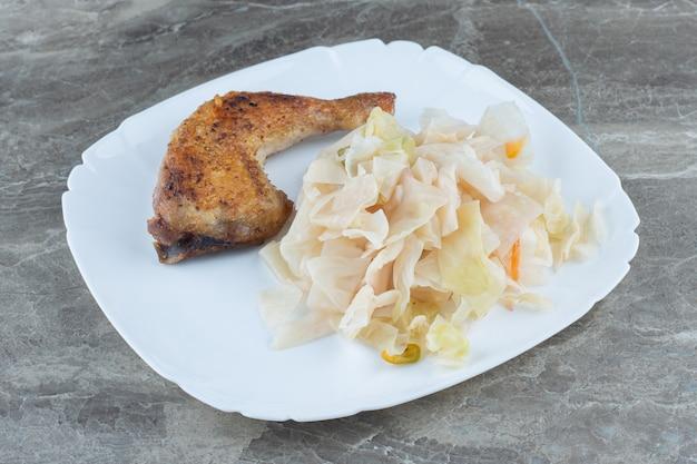 Posiekana biała kapusta ogórkowa z grillowanym udkiem z kurczaka.