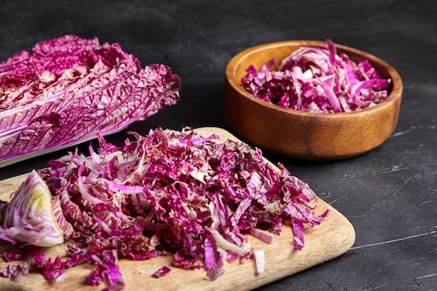 Posiekana czerwona kapusta pekińska (fioletowy wombok) na drewnianą deskę do krojenia i miska na stole. red napa