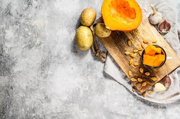 Posiekana dynia na rustykalnej desce do krojenia. składniki na zupę dyniową. posiekana dynia na rustykalnej desce do krojenia. smaczne i zdrowe jedzenie. wegańskie jedzenie
