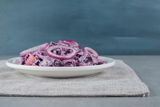 Posiekana fioletowa cebula i surówka z kapusty na białym talerzu ceramicznym.