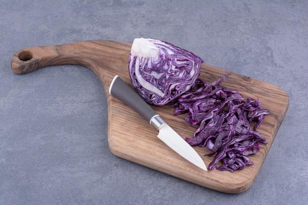 Posiekana kapusta fioletowa na drewnianym talerzu.