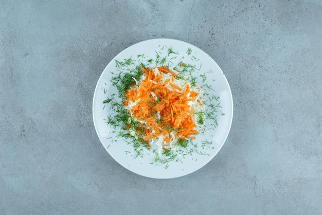 Posiekana kapusta i marchewki na białym talerzu.