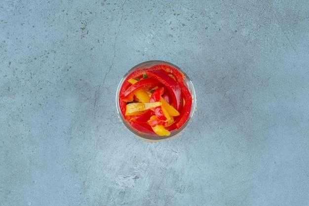Posiekana wielokolorowa papryka w szklanym kubku.