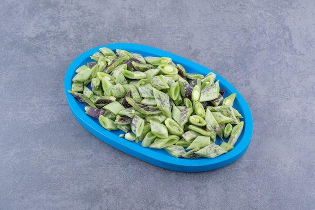 Posiekana zielona fasola na patelni na niebieskiej powierzchni
