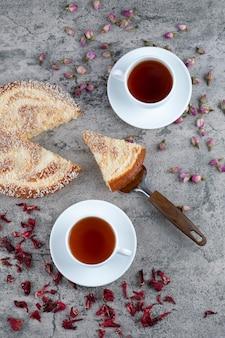 Posiekane okrągłe pyszne ciasto z filiżankami herbaty ustawionymi na marmurowym stole.