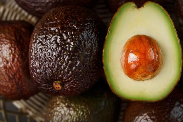 Posiekane pestki i całe organiczne awokado hass z bliska