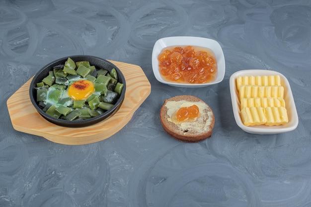 Posiekane strączki fasoli z jajecznicą, maślanką, plastrami masła i konfiturą z białej wiśni na marmurowym stole.