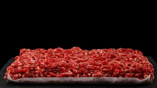 Posiekane surowe mięso na czarnej ścianie.