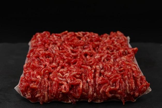 Posiekane surowe mięso na czarnym tle.