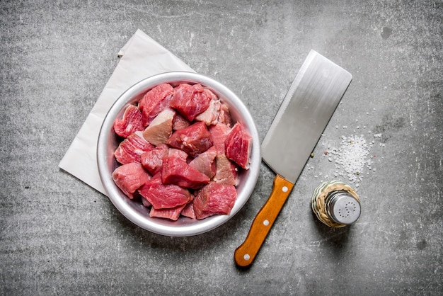 Posiekane surowe mięso nożem rzeźniczym i solą na kamiennym stole