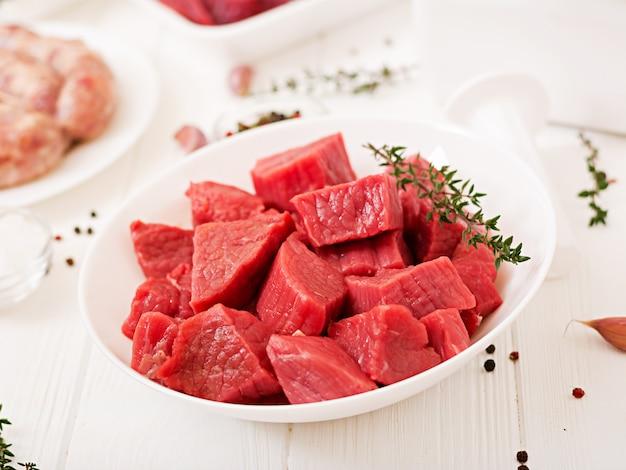 Posiekane surowe mięso. proces przygotowania farszu za pomocą maszynki do mięsa. kiełbasa domowa. mielona wołowina.