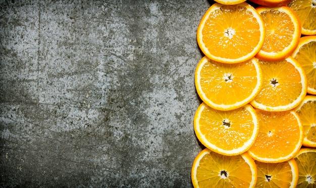 Posiekane świeże pomarańcze. na kamiennym stole. widok z góry. wolne miejsce na tekst. widok z góry