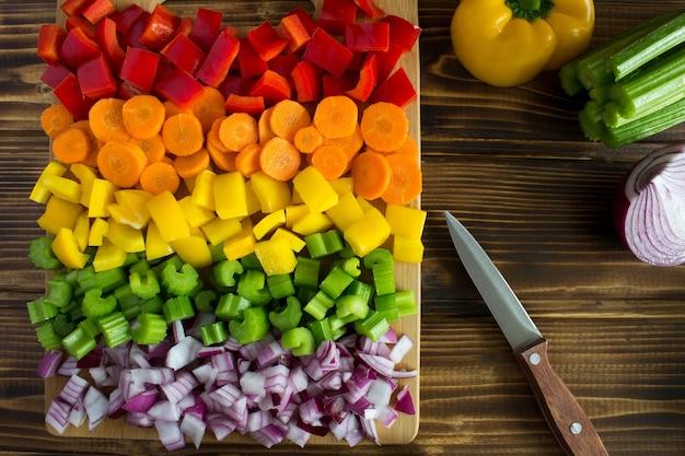 Posiekane świeże Warzywa Na Deskę Do Krojenia Na Brązowym Tle Drewnianych. Widok Z Góry. Premium Zdjęcia