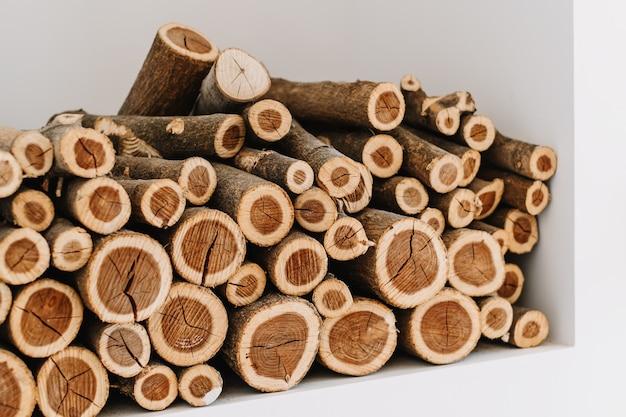 Posiekane ułożone drewno opałowe na półce w białej ścianie.