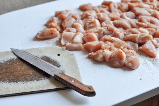 Posiekany filet z kurczaka nożem na stole
